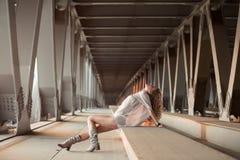 Schöne gelockte junge Frau, die auf industriellem Brückenstandort aufwirft Lizenzfreie Stockbilder