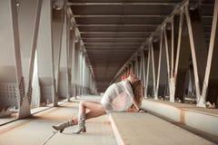 Schöne gelockte junge Frau, die auf industriellem Brückenstandort aufwirft Stockbild