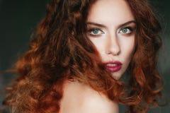 Schöne gelockte rothaarige junge Frau in einem schwarzen Korsett Lizenzfreies Stockbild