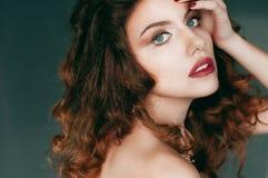 Schöne gelockte rothaarige junge Frau in einem schwarzen Korsett Stockfotografie
