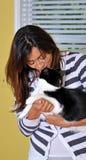 Schöne gemischtrassige Frau, die Katze küßt Stockfoto