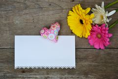 Schöne Gerberas floewrs mit farbigem Herzen und Weißbuch für Ihren Text auf Holz Stockfotos