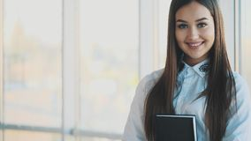 Schöne Geschäftsdame betrachtet Kamera und lächelt beim Arbeiten im Büro stock footage