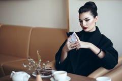 Schöne Geschäftsdame mit perfektem bilden Sitzen im netten Café und das Betrachten ihres Telefons stockbild