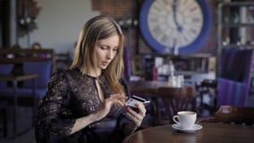 Schöne Geschäftsfrau bestellt die Karten für ein Flugzeug, das on-line ist und sitzt in einem Café Das Mädchen verwendet Onlineba stock footage