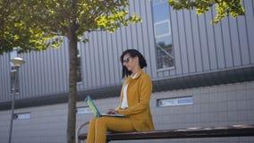 Schöne Geschäftsfrau in der Sonnenbrille und Klage unter Verwendung des Laptops auf einem Bruch, der draußen nahe auf der Bank im stock video