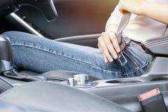 Schöne Geschäftsfrau, die auf Autositz und befestigendem Sicherheitsgurt sitzt lizenzfreie stockfotos
