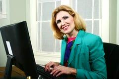 Schöne Geschäftsfrau, die auf Computer lächelt und schreibt Stockbilder