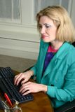 Schöne Geschäftsfrau, die auf Computer schreibt lizenzfreie stockbilder