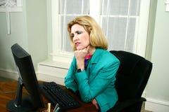 Schöne Geschäftsfrau, die Computer denkt und betrachtet Stockfotos