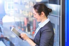 Schöne Geschäftsfrau, die eine Tablette, vor Fenstern in O verwendet lizenzfreies stockbild