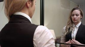 Schöne Geschäftsfrau, die fertig wird, eine Weste, ihr Selbst überprüfend heraus in den Spiegel an einsetzen zu lassen stockfotografie