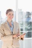 Schöne Geschäftsfrau, die ihren Tabletten-PC verwendet und am camer lächelt Stockbild