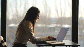 Schöne Geschäftsfrau, die am Laptop im Büro arbeitet stock video