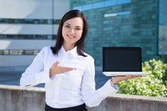 Schöne Geschäftsfrau, die Laptop mit leerem Bildschirm zeigt stockfotos