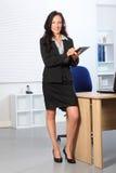 Schöne Geschäftsfrau, die mit Klemmbrett steht Stockbild