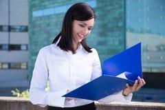 Schöne Geschäftsfrau, die Ordner mit Dokumenten hält Stockbilder