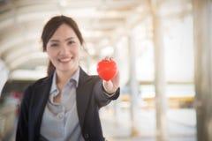 Schöne Geschäftsfrau, die roten Herzfokus auf Händen hält Stockfotografie