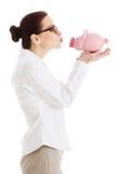 Schöne Geschäftsfrau, die Sparschwein hält. Stockfoto