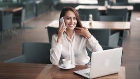 Schöne Geschäftsfrau, die am Telefon im Café, Laptop auf Tabelle, Zeitlupe spricht stock footage