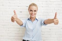 Schöne Geschäftsfrau, die zwei Daumen lächelt und aufgibt Lizenzfreie Stockbilder