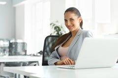 Schöne Geschäftsfrau in ihrem Büro, das an Laptop-Computer arbeitet Stockbild