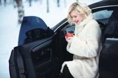 Schöne Geschäftsfrau im luxuriösen weißen Pelzmantel heißen Kaffee am Tag des verschneiten Winters trinkend, der in ihrem Auto si Stockfotografie