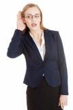 Schöne Geschäftsfrau ist die über- Anhörung und trouching ihr Ohr. stockbilder