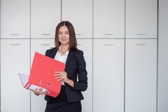 Schöne Geschäftsfrau steht mit einem roten Ordner in den Händen in einem Büro lizenzfreie stockfotos