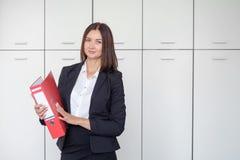 Schöne Geschäftsfrau steht mit einem roten Ordner in den Händen in einem Büro stockbild