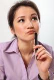 Schöne Geschäftsfrau tief im Gedanken mit Feder Lizenzfreie Stockfotografie