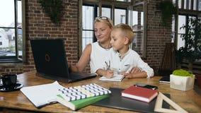 Schöne Geschäftsfrau von mittlerem Alter, die an Laptop arbeitet, wenn ihr kleiner reizender Enkel etwas in ein Notizbuch an schr stock video