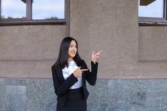 Schöne Geschäftsfrau zeigt mit beiden Händen auf möglichem plac stockfotos