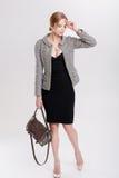 schöne Geschäftsfraublondine im schwarzen Kleid, in der Jacke und in den purs Stockfotos