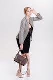 schöne Geschäftsfraublondine im schwarzen Kleid, in der Jacke und in den purs Lizenzfreie Stockfotografie