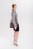 schöne Geschäftsfraublondine im schwarzen Kleid, in der Jacke und in den purs Lizenzfreie Stockfotos