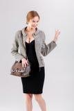 schöne Geschäftsfraublondine im schwarzen Kleid, in der Jacke und in den purs Stockbild