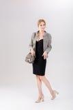 schöne Geschäftsfraublondine im schwarzen Kleid, in der Jacke und in den purs Lizenzfreie Stockbilder