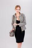 schöne Geschäftsfraublondine im schwarzen Kleid, in der Jacke und in den purs Stockfotografie