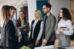 Schöne Geschäftsleute benutzen Geräte, sprechen und lächeln während der Konferenz im Büro stockfotos