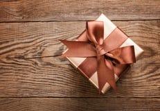Schöne Geschenkbox mit einem Bogen auf dem Tisch von den alten Brettern stockfotos