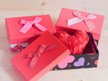 Schöne Geschenke mit reizendem Herzen auf hölzernem Hintergrund Stockfotografie