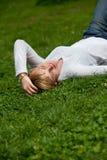 Schöne gesunde junge Frau, die auf dem Gras liegt Stockfotografie