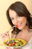 Schöne gesunde junge Frau, die einen frischen Garten-Salat isst Stockfotografie