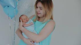 Schöne gesunde Mutter, die ihr neugeborenes Kind hält Küssen des Schätzchens stock footage