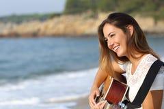 Schöne Gitarristfrau, die Gitarre auf dem Strand spielt Lizenzfreie Stockfotografie