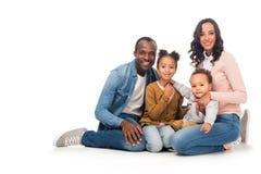 schöne glückliche Afroamerikanerfamilie mit zwei Kindern, die an der Kamera lächeln lizenzfreie stockfotografie