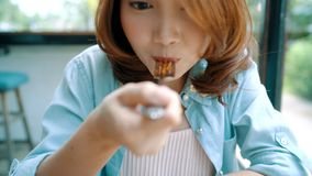 Schöne glückliche Asiatin, die eine Platte von italienischen Meeresfrüchtespaghettis am Restaurant oder am Café beim Lächeln und  stock video