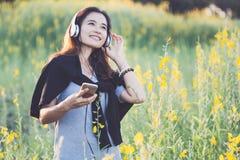 Schöne glückliche asiatische Frau, die auf dem gelben Gebiet genießt stockfotos