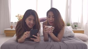 Schöne glückliche asiatische lesbische Paare sind Abnutzungspyjamas unter Verwendung des Smartphone für die Prüfung von Nachricht stock footage